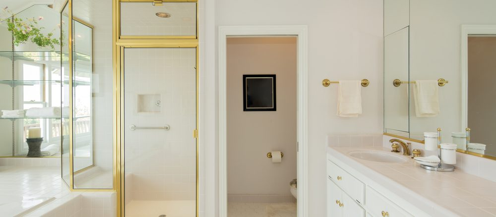 Lyxigt badrum med gulddetaljer - investera i din badrumsrenovering